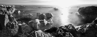 Sea Rocks on the Ocean Shore. A long exposure of ocean water between sea rocks at the beach with beautiful clouds above the horizon. Black and white infrared Stock Photography