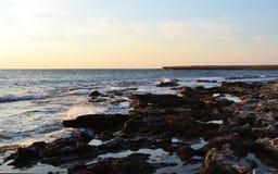 Sea and rocks. Rocky seashore westering, waves batter against rocks Stock Image