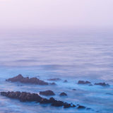 Sea and rocks before sunrise. Sea waves hitting the rocks before sunrise at Mossel Bay in South Africa Royalty Free Stock Photo