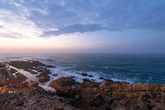 Sea and rocks before sunrise. Sea waves hitting the rocks before sunrise at Mossel Bay in South Africa Stock Image