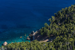 Sea rocks and transparent sea. Sea waves and rocks on the steep west coast of Mallorca Stock Images