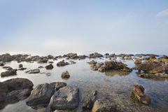Sea and rocky coast in the morning Stock Images