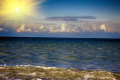 Sea rolling and receding water in rays of setting sun. Stock Photo