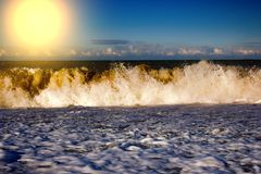 Sea rolling and receding water in rays of setting sun. Royalty Free Stock Image