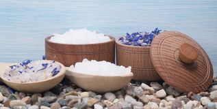 Sea salt with the addition of blue flowers, on small stones, on a blue background Royalty Free Stock Photos