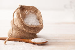 Sea salt in the bag and wooden spoon on white Royalty Free Stock Photos