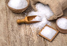 Sea salt in the bag. And with wooden spoon on wooden background royalty free stock photo