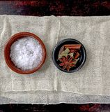Sea salt, star anise, bay leaf, black cardamom and cinnamon stick arranged in two small bowls atop cheesecloth. Sea salt, bay leaf, star anise, black cardamom stock image