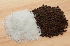 Sea salt and black peppercorn. Sea salt and black pepercorn on wood table royalty free stock photos