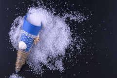 Sea salt in a blue paper bag is scattered on a black background. Royalty Free Stock Photography