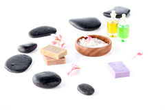 Sea salt in bowl, black spa stones and orchid petals isolated on white Stock Images