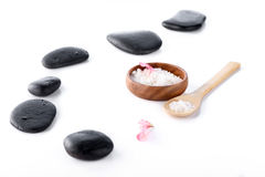 Sea salt in bowl, black spa stones and orchid petals isolated on white Stock Photos
