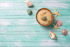 Sea salt in bowl with sea objects  on turquoise wooden backgroun. Spa setting. Sea salt in bowl with sea objects  on turquoise wooden background. Selective focus Royalty Free Stock Images