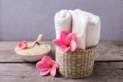 Sea salt in bowl, towels and flowers on  rustic  wooden  backgro Stock Photography