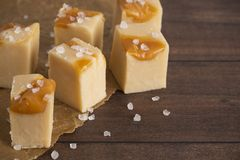 Salted Caramel Fudge on a Wooden Table with Baking Paper royalty free stock image