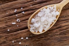 Crystal sea salt in a wooden spoon on dark vintage wooden background, top view, close-up, selective focus. Sea salt crystals in a wooden spoon on dark vintage Royalty Free Stock Photography