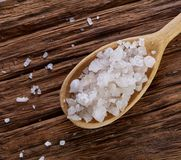 Crystal sea salt in a wooden spoon on dark vintage wooden background, top view, close-up, selective focus. Sea salt crystals in a wooden spoon on dark vintage Stock Photography
