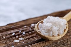 Crystal sea salt in a wooden spoon on dark vintage wooden background, top view, close-up, selective focus. Sea salt crystals in a wooden spoon on dark vintage Royalty Free Stock Photos