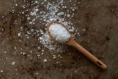 Sea Salt Flakes spilled from wooden spoon stock photos