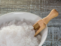 Sea salt flakes and wooden spoon over bark on wooden background. Himalayan Halite salt condiment macro view. Natural mineral flavoring food preservative, Saline royalty free stock photography