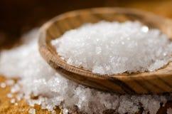 Sea Salt - Fleur De Sel. Close up of sea salt and wooden spoon on a background of sea salt stock photography