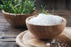 Sea salt and green rosemary on the wooden table Royalty Free Stock Images