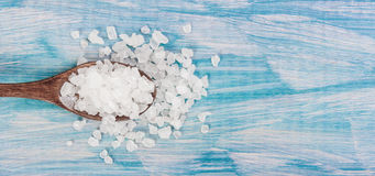Sea salt grind on wooden light blue shabby table wooden spoon. Kitchen and cosmetic healthy usage. , closeup, free space Stock Photos