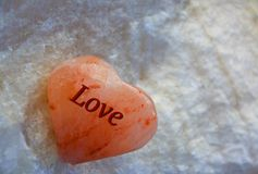 SEA SALT HEALING HEART. HIMALAYAN SEA SALT HEART RESTING ON A SLAB OF ONYX CRYSTAL Royalty Free Stock Photo