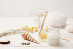 Sea salt, herbs to recipes, as the foam on a white wooden backgr Stock Photos