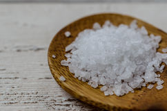 Sea salt. Natural sea salt on wooden spoon and wooden floor background Stock Photo