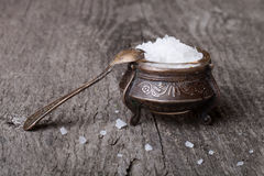 Sea salt in an old utensils and a small spoon on a wooden table