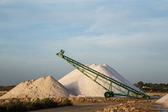 Sea salt piles and conveyor belt Stock Photography