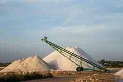 Sea salt piles and conveyor belt Stock Photography