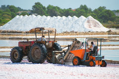 Sea salt production. Salt evaporation pond with tractor Royalty Free Stock Image