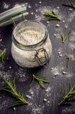 Sea salt with rosemary and lemon zest on black slate board. Stock Image