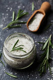 Sea salt scented herb rosemary on black stone background Stock Photos