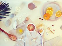 Sea salt, sliced orange, egg, sea stones and shells on a bright table, top view, ingredients for a mask, scrub. Gentle care procedures stock photo