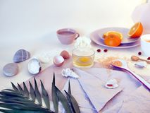 Sea salt, sliced orange, egg, sea stones and shells on a bright table, top view, ingredients for a mask, scrub. Gentle care procedures royalty free stock images