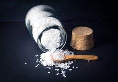 Sea salt with spoon and jar on dark background Stock Photo