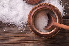 Crystals of sea salt on a wooden table. Sea salt in a wooden keg. Crystals of sea salt on a wooden table Stock Photo