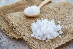 Sea salt in wooden spoon on burlap sack Royalty Free Stock Photo