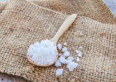 Sea salt in wooden spoon on burlap sack Royalty Free Stock Images