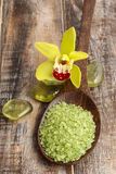 Sea salt on wooden spoon, orchid flowers in the background Stock Image