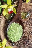 Sea salt on wooden spoon, orchid flowers in the background Stock Photography