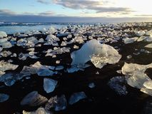 Sea sand sun and ice in South Iceland. Black beach nearby Jokulsalon, large glacier lagoon in South Iceland Stock Images