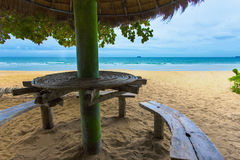 Sea sand and sun looking from beautiful and peaceful beach under big green tree. The beach has sitting area bench and little cocon. Ut huts little far behind is Royalty Free Stock Photo