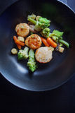 Sea Scallops with vegetables on a black plate. Seafood, healthy eating Royalty Free Stock Photography