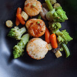 Sea Scallops with vegetables on a black plate. Seafood, healthy eating Stock Photo