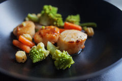 Sea Scallops with vegetables on a black plate. Seafood, healthy eating Royalty Free Stock Photos