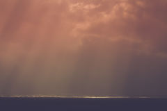 Sea scape. A dark, moody seascape with rays of sunlight Stock Image
